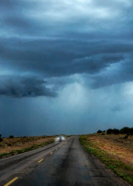 Jill Battaglia CAR ON COUNTRY ROAD WITH STORMY SKY