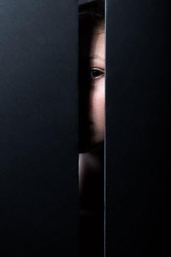 Magdalena Russocka young woman staring through gap in wall
