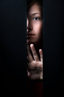 Magdalena Russocka scared young woman staring through gap in wall