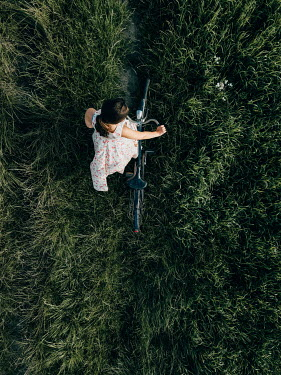 Magdalena Russocka young woman with bicycle in meadow from above