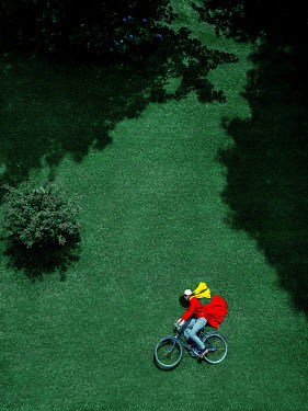 Magdalena Russocka forced perspective of man riding bicycle from above