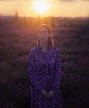 Svitozar Bilorusov WOMAN STANDING IN LAVENDER FIELD AT SUNSET