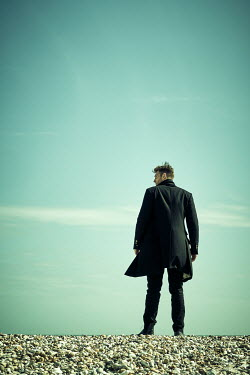 CollaborationJS MAN IN COAT STANDING ON BEACH