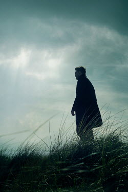 CollaborationJS MAN WITH COAT IN DUNES AT DUSK
