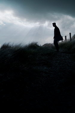 CollaborationJS SILHOUETTED MAN IN SAND DUNES AT DUSK