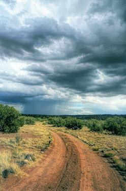 Jill Battaglia EMPTY DUSTY COUNTRY ROAD WITH STORMY SKY
