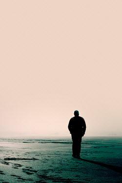 Joanna Jankowska SILHOUETTED MAN STANDING ON BEACH AT DUSK