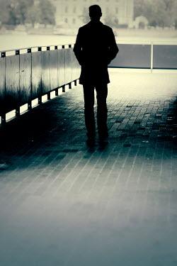 Joanna Jankowska SILHOUETTED MAN STANDING ON URBAN WALKWAY