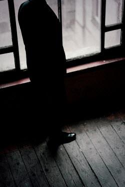Joanna Jankowska MAN STANDING BY WINDOW IN OLD BUILDING
