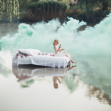 Jovana Rikalo BLONDE WOMAN ON BED IN LAKE WITH GREEN SMOKE