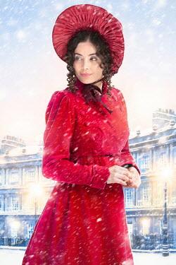 Lee Avison regency woman wearing a red coat and bonnet in the snow