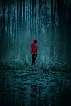 Natasza Fiedotjew man in red coat standing by pond in woods at night