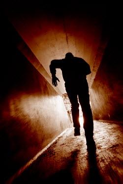 Tim Robinson SILHOUETTED MAN RUNNING IN CONCRETE PASSAGEWAY