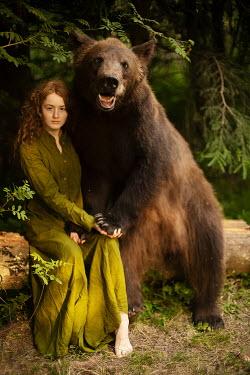 Alexandra Bochkareva WOMAN AND BEAR SITTING ON LOG IN FOREST