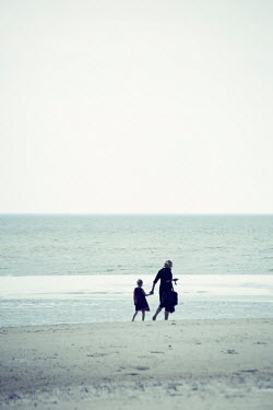 Carmen Spitznagel MOTHER AND DAUGHTER HOLDING HANDS ON BEACH