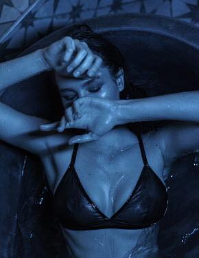 Maria Yakimova WOMAN IN UNDERWEAR LYING IN BATH IN SHADOW
