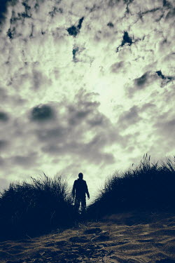 Tim Robinson SILHOUETTED MAN STANDING ON SAND DUNES AT DUSK