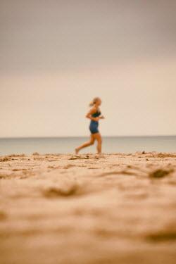 Tim Robinson BLONDE WOMAN RUNNING ON SANDY BEACH