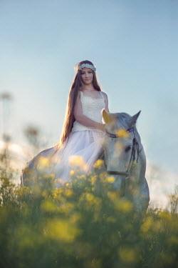 Carmen Spitznagel WOMAN IN WHITE ON HORSE IN MEADOW