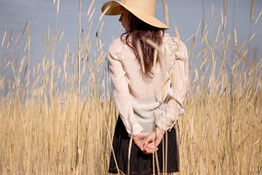 Michael Nelson GIRL WITH HAT STANDING IN FIELD OF GOLDEN GRASS