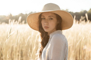 Michael Nelson GIRL WITH HAT IN FIELD OF GOLDEN GRASS