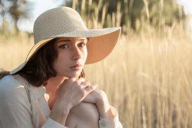 Michael Nelson GIRL WITH HAT SITTING IN FIELD OF GOLDEN GRASS