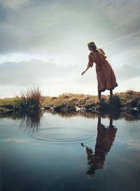Mark Owen WOMAN WATCHING RIPPLES IN RIVER