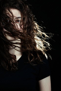 Magdalena Russocka close up of young woman with dark hair covering her face inside