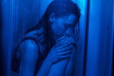 Maria Yakimova SAD WOMAN SITTING BEHIND DOOR IN SHOWER