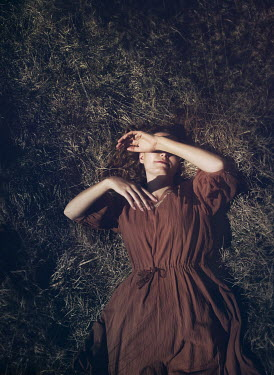 Mark Owen WOMAN LYING ON GRASS WITH HAND COVERING FACE