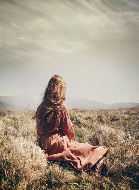 Mark Owen WOMAN WITH LONG BROWN HAIR SITTING IN COUNTRYSIDE