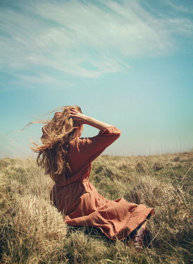 Mark Owen WOMAN WITH LONG HAIR SITTING IN WINDY COUNTRYSIDE