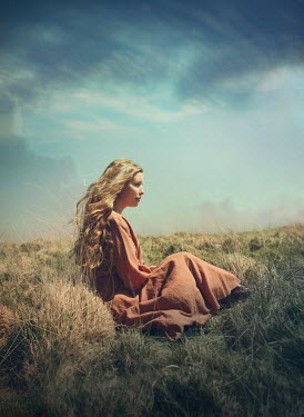 Mark Owen SERIOUS GIRL WITH LONG HAIR SITTING IN COUNTRYSIDE