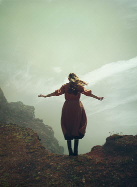 Mark Owen WOMAN STANDING ON EDGE OF CLIFF