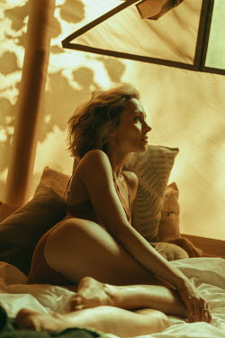 Maria Yakimova WOMAN LYING ON BED WITH GOLDEN LIGHT