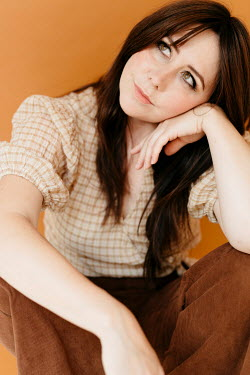 Shelley Richmond WOMAN WITH LONG BROWN HAIR SITTING DAYDREAMING