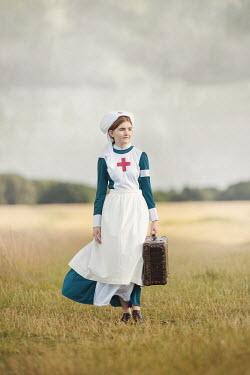 Anna Buczek HISTORICAL NURSE WITH SUITCASE WALKING IN FIELD