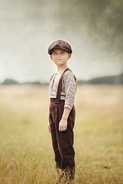 Anna Buczek YOUNG SERIOUS BOY IN CAP STANDING IN FIELD