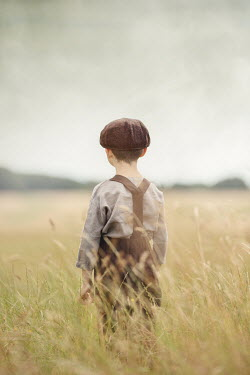 Anna Buczek YOUNG BOY IN CAP STANDING IN FIELD