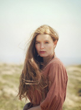 Mark Owen SERIOUS WOMAN WITH LONG HAIR IN FIELD
