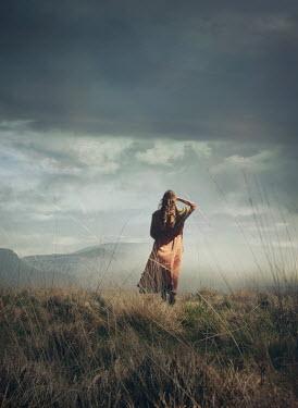 Mark Owen WOMAN STANDING IN FIELD WATCHING LANDSCAPE
