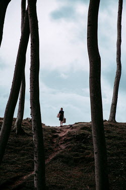 Natasza Fiedotjew silhouette of woman holding suitcases among trees