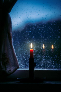 Natasza Fiedotjew lit candle in candlestick standing on windowsill at night