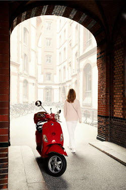 Kerstin Marinov WOMAN WALKING THROUGH ARCHWAY BY RED SCOOTER