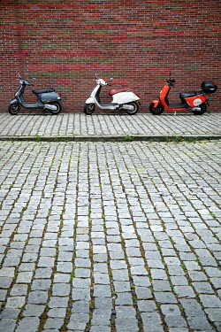Kerstin Marinov THREE SCOOTERS PARKED IN COBBLED STREET