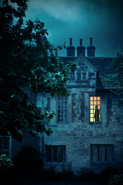 Miguel Sobreira SILHOUETTED MAN IN WINDOW OF VICTORIAN HOUSE AT DUSK