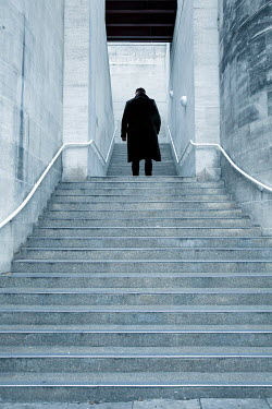 Miguel Sobreira MAN IN COAT OUTDOORS ON STEPS