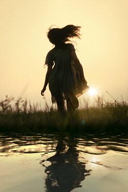 Magdalena Russocka teenage girl running by river at sunset