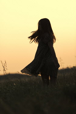 Magdalena Russocka teenage girl standing in field at sunset