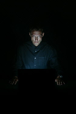 Magdalena Russocka serious mature man wearing black shirt sitting at laptop in dark room